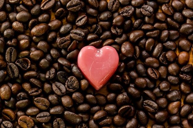 Valentinstag hintergrund. rosa liebesherz auf kaffeebohne