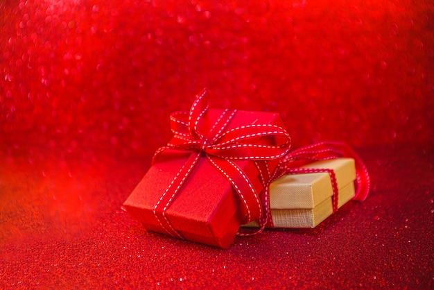 Valentinstag hintergrund. rote geschenkboxen mit festlichem band, auf glänzendem hintergrund des roten bokeh. geburtstagsgrußkarte, valentinstag