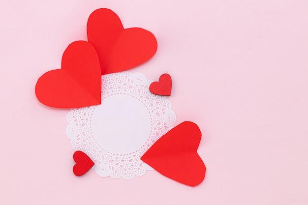 Valentinstag hintergrund. rote herzen auf pastellrosa hintergrund. valentinstag konzept. flache lage, draufsicht, kopierraum