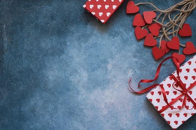 Valentinstag hintergrund. rote herzen und geschenkboxen auf blauem hintergrund. speicherplatz kopieren, draufsicht