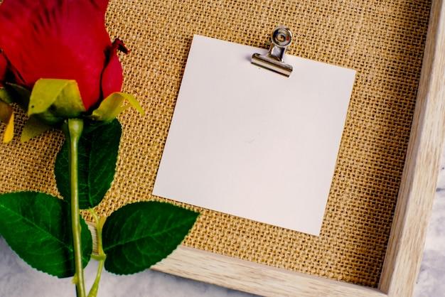Valentinstag hintergrund. rote rose mit nachrichtenkarte des liebesromantikpaares.
