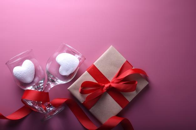 Valentinstag hintergrundgrußkarte liebessymbole, rote dekoration mit gläsern. draufsicht mit kopierraum und text. flache lage