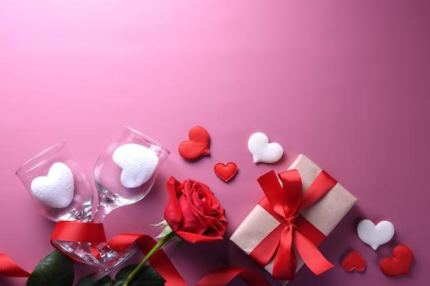 Valentinstag hintergrundgrußkarte liebessymbole, rote dekoration mit gläsern herz rosen geschenke. draufsicht mit kopierraum und text. flache lage