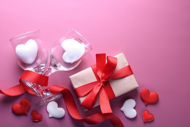 Valentinstag hintergrundgrußkarte liebessymbole, rote dekoration mit gläsern herz rosen geschenke. draufsicht