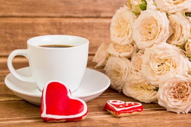 Valentinstag. hochzeit. eine tasse kaffee und zwei lebkuchenherz