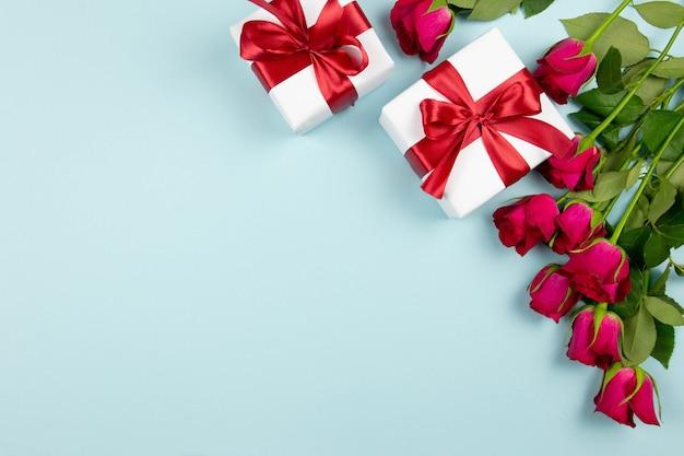 Valentinstag, hochzeit oder muttertag wohnung lag mit geschenkboxen mit rotem band, rosen und herzen auf pastellblau.