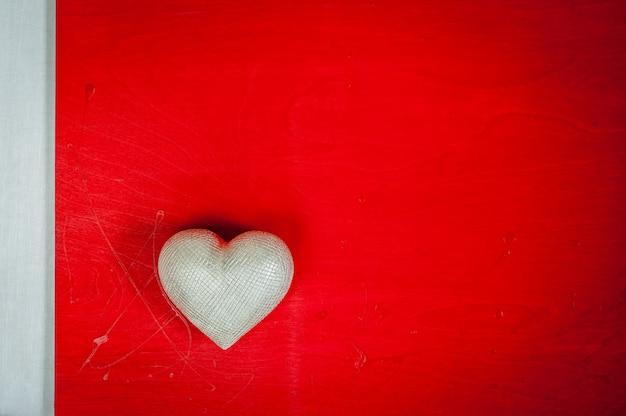 Valentinstag. hochzeitstag. silbernes herz auf rotem hölzernem hintergrund.