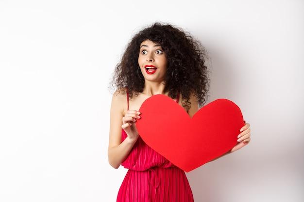 Valentinstag. junge frau, die links überrascht sah, etwas erstaunliches am tag des liebenden sah, fand wahre liebe, hielt großes rotes herz auf brust, weißer hintergrund.