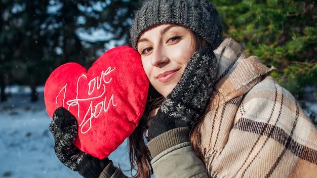 Valentinstag. junge frau hält rotes kissenherz, das mit ich liebe dich geformt wird, schreibend in winterwald