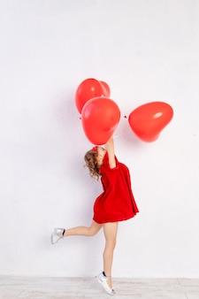 Valentinstag kinder. kleines mädchen im roten kleid, das herzförmige luftballons hält