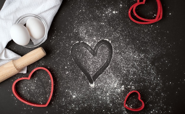 Valentinstag-kochkomposition mit dem finger gezeichneten herzen auf dem verstreuten mehl auf dem dunklen hintergrund. flache lage, draufsicht.