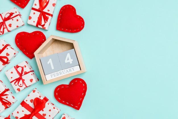 Valentinstag-komposition aus geschenkboxen, holzkalender und roten textilherzen