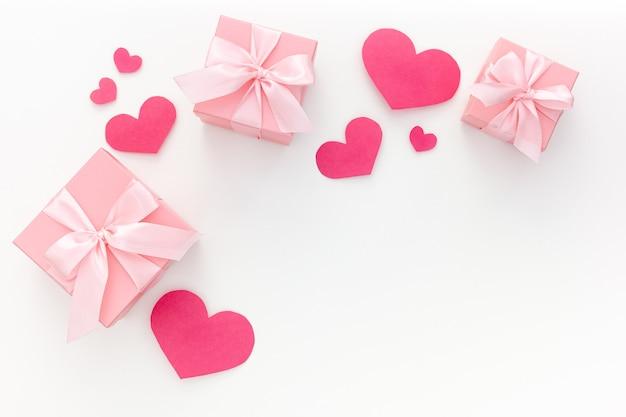 Valentinstag komposition: drei rosa geschenkboxen mit band und papierherzen