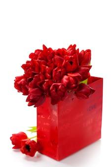 Valentinstag komposition mit einkaufstasche und roten tulpen