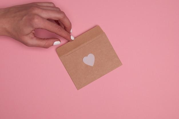 Valentinstag komposition mit kopierraum. frauenhand, die umschlagpostkarte mit weißem konfettiherz auf pastellhintergrund hält. nahaufnahme, draufsicht, kopierraum