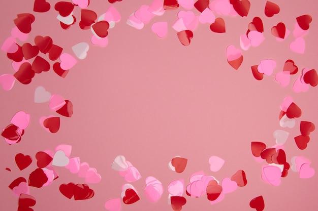 Valentinstag komposition mit kopierraum. rahmen aus konfettiherzen rot und rosa auf pastellhintergrund. nahaufnahme, draufsicht, kopierraum