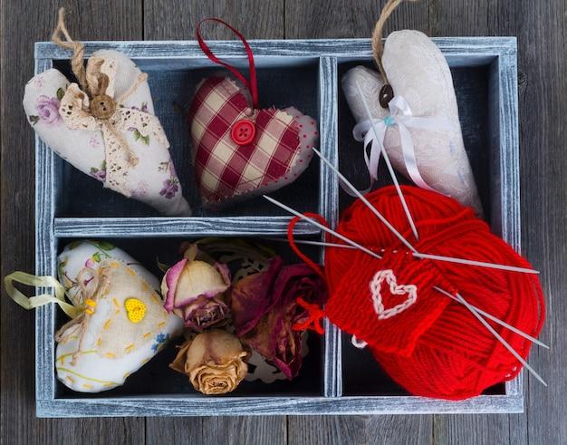Valentinstag komposition mit tilda herzen, stricken und getrockneten blumen in einer holzkiste. rustikaler stil. draufsicht. selektiver fokus.