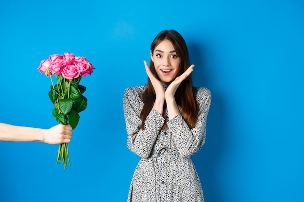 Valentinstag-konzept. aufgeregte und glückliche junge frau, die erstaunt in die kamera schaut, während die hand mit blumenstrauß die hand ausstreckt und ein romantisches geschenk erhält, blauer hintergrund