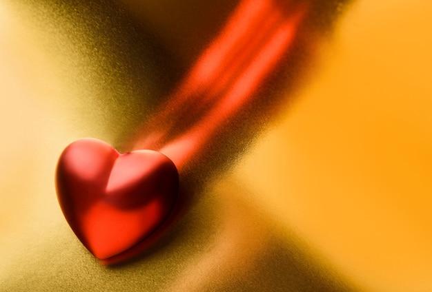 Valentinstag konzept. das herz liegt auf einem glänzenden goldenen hintergrund. Premium Fotos