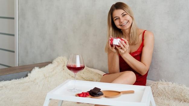 Valentinstag konzept. festliches frühstück. die blondine hält ein geschenk auf einem weißen tablett mit süßigkeiten, schokolade und wein