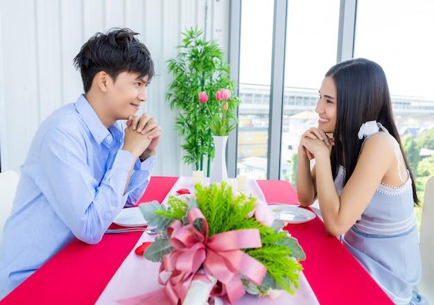 Valentinstag-konzept, glückliches asiatisches junges süßes paar, das das mittagessen mit einem rosenstrauß im restaurant romantisch hat