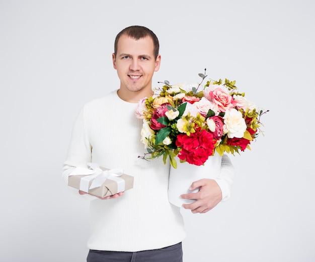 Valentinstag-konzept - gutaussehender mann, der blumenstrauß und geschenkbox über grauem hintergrund hält