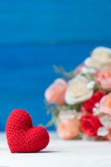 Valentinstag-konzept. hand machen rotes herz des garns vor rosafarbenem blumenstrauß auf holztisch