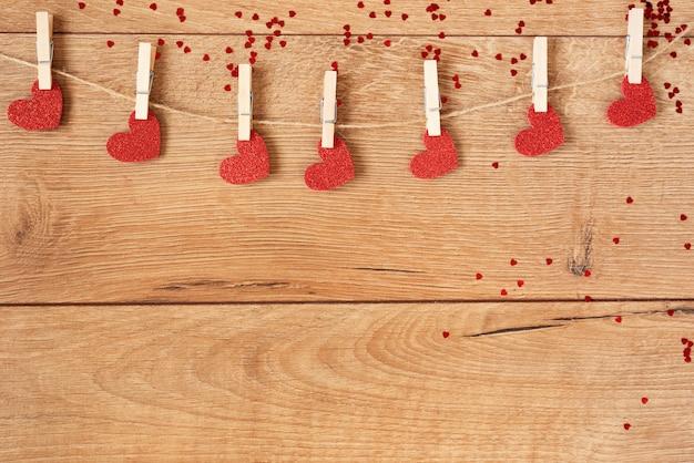 Valentinstag konzept. herzform girlande. rote glitzerherzen hängen am seil auf holz