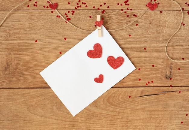 Valentinstag konzept. herzform girlande. rote glitzerherzen und brief hängen am seil auf holz