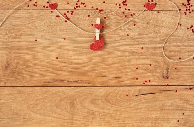 Valentinstag konzept. herzform girlande. rotes glitzerherz, das am seil auf holz hängt