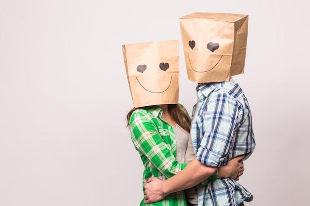 Valentinstag-konzept - junges liebespaar mit taschen über den köpfen auf weißem hintergrund