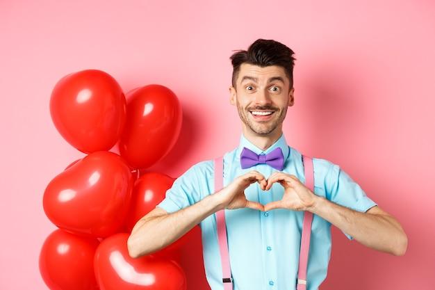 Valentinstag konzept romantischer kerl in fliege zeigt herzgeste und sagt, ich liebe dich mit hoffnungsvollen ...