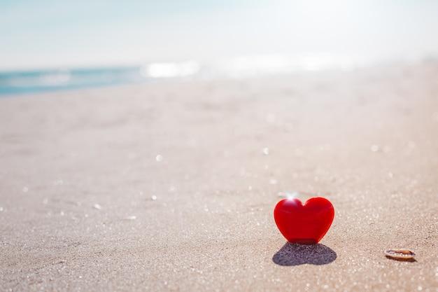Valentinstag konzept. romantisches liebessymbol des roten herzens auf dem sandstrand mit kopienraum. vorlage für inspirierende kompositionen und zitatpostkarten.