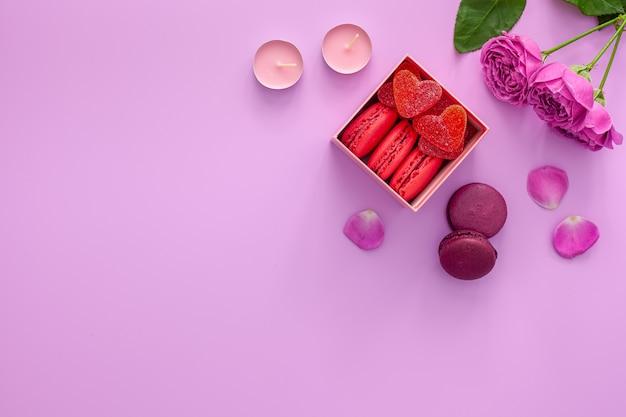 Valentinstag konzept. rosa schachtel mit marmelade und makronen und einer schönen rose auf einem rosa tisch