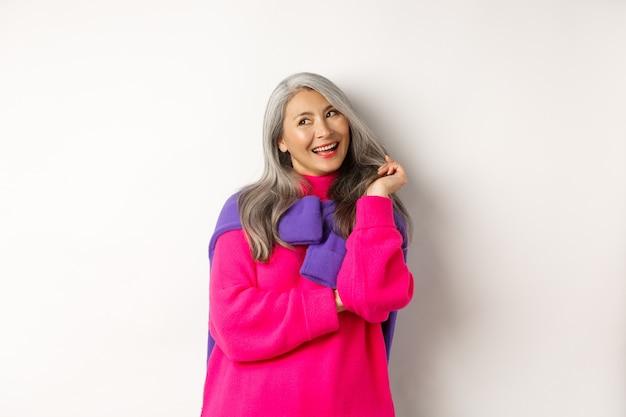 Valentinstag-konzept. schöne asiatische seniorin, die kokett lacht, mit haarsträhnen spielt und die obere linke ecke flirty betrachtet, auf weißem hintergrund stehend