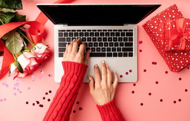 Valentinstag konzept. weibliche hände, die auf der tastatur tippen