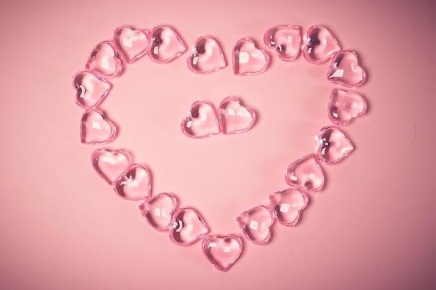 Valentinstag-konzept. zwei rote herzen in einer umgebung transparente glasherzen auf rosa hintergrund, glasherz glüht, glasmalerei. viele rote glasherzen. liebe zum valentinstag. platz kopieren.