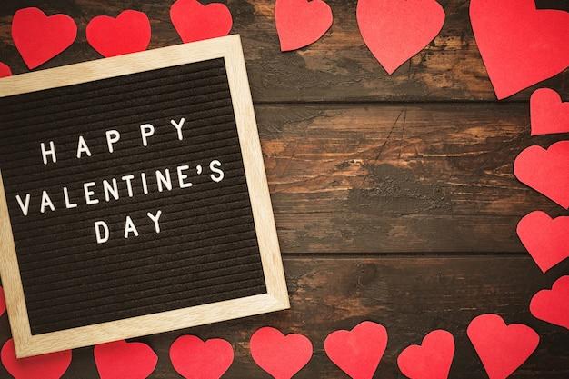 Valentinstag-konzeptmodell. glückliche valentinstagwörter auf schwarzem briefbrett mit dekorativen roten herzen als rahmen auf hölzernem hintergrund.