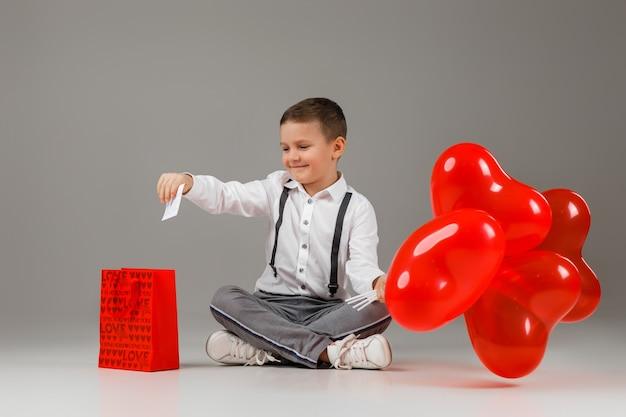 Valentinstag. lächelnder stilvoller kinderjunge hält rote herzförmige luftballons und legt eine liebesnotiz in geschenkpapiertüte