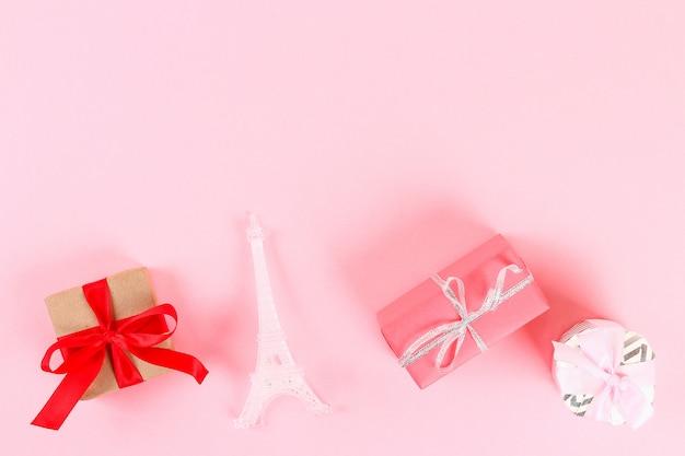 Valentinstag-layout. geschenke, herzen, eiffelturm auf einem rosa pastellhintergrund. valentinstag