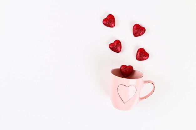 Valentinstag-layout. rosa becher mit abgehenden herzen auf einem weißen hintergrund. valentinstag