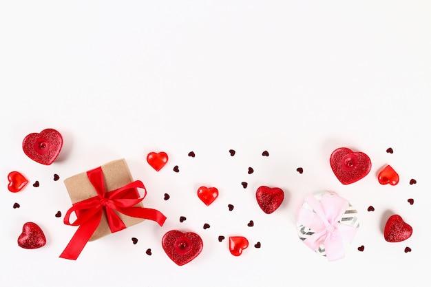 Valentinstag-layout. rosa geschenk mit herzen, kerzen und konfetti auf einem weißen hintergrund.