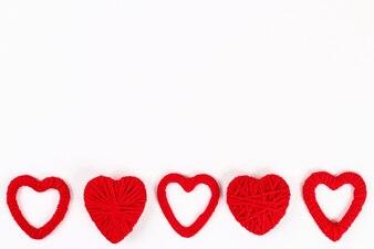 Valentinstag-Layout. Rote selbst gemachte diy Herzen gemacht von der Pappe und vom Garn