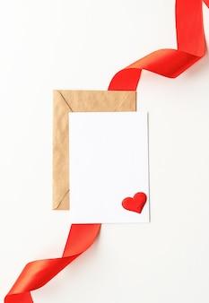 Valentinstag. leere grußkarte mit umschlag und mock-up-vorlage des roten bandes für valentinstag