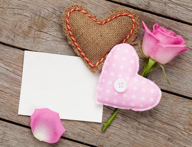 Valentinstag leere grußkarte oder fotorahmen mit handgemachten spielzeugherzen und rosa rose