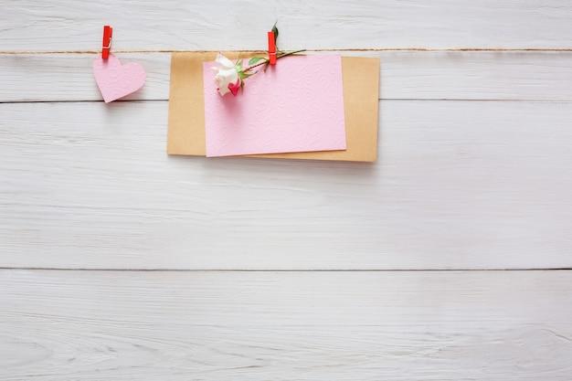 Valentinstag, leere grußkarte und rosenblume auf wäscheklammer auf weißem rustikalem holz auf holztisch