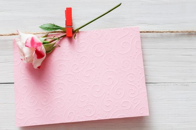 Valentinstag, leere grußkarte und rosenblume auf wäscheklammer auf weißen rustikalen holzbrettern