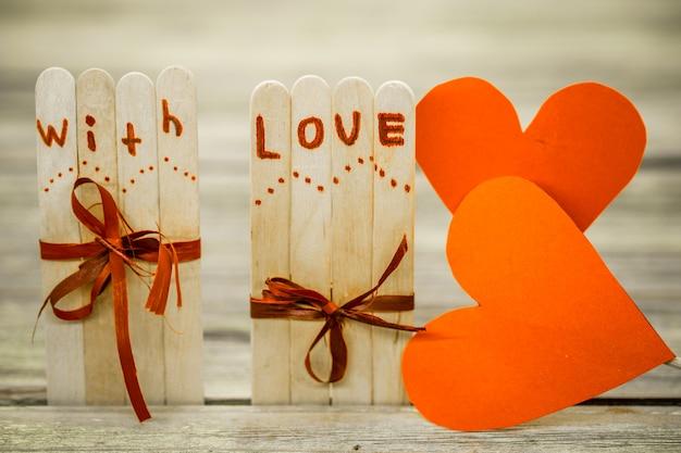 Valentinstag lieben inschrift auf kleinen holzstöcken mit herz