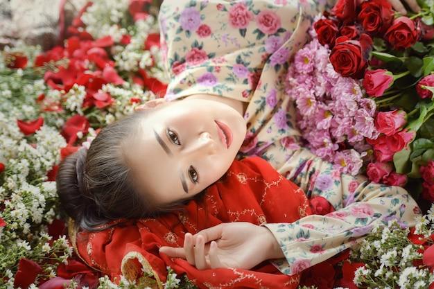 Valentinstag. liebendes mädchen. das mädchen in einem roten kleid liegt auf dem boden in den blütenblättern roter rosen. schöne frau mit roten rosenblättern,
