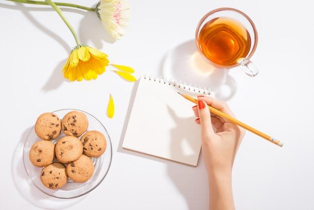 Valentinstag liebesbrief auf holzuntergrund. rote samtherzformplätzchen, süßigkeiten und kaffee. weibliche hände mit rotem nagellack